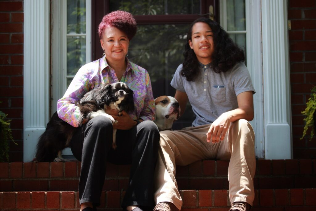 Stephanie, her son Alexander, and their two dogs sitting on their front step